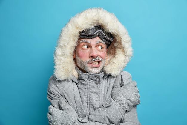 Foto de un hombre europeo que tiembla de frío después de ir a patinar cruza las manos sobre el cuerpo intenta calentarse viste chaqueta de invierno gris con capucha de piel y guantes con la cara congelada cubierta por hielo