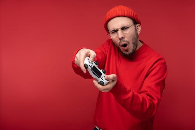 Foto de hombre feliz con barba en ropa roja tiene joystick jugando al ganador del juego con el objetivo de ganar y éxito, aislado sobre fondo rojo.