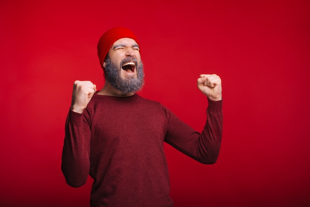 Foto de hombre feliz celebrando el éxito y sosteniendo el balón de fútbol