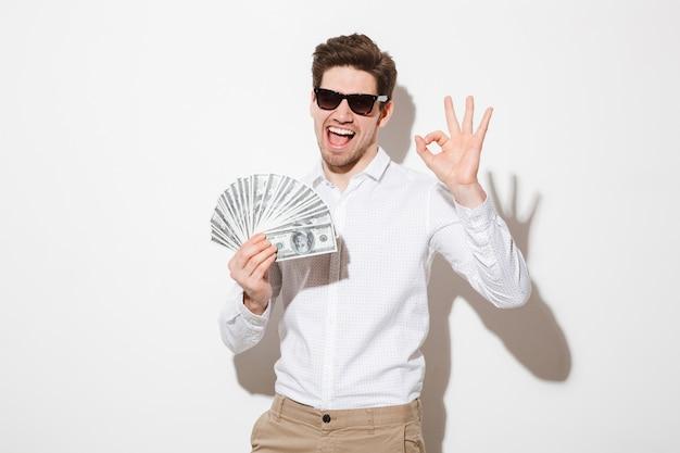 Foto de hombre feliz ganador en camisa y gafas de sol sonriendo sosteniendo abanico de dinero en billetes de dólar y mostrando el símbolo ok, aislado sobre una pared blanca con sombra