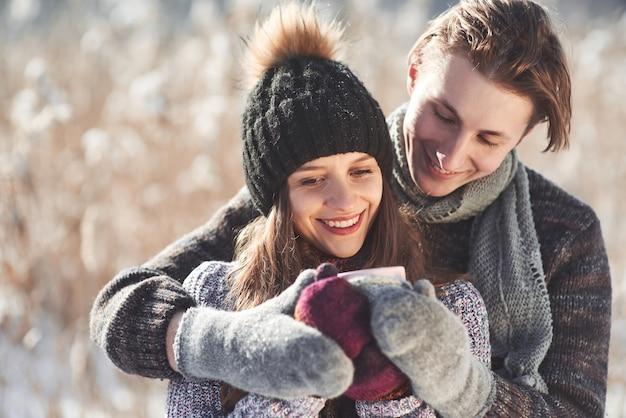 Foto de hombre feliz y mujer bonita con tazas al aire libre en invierno. vacaciones de invierno y vacaciones