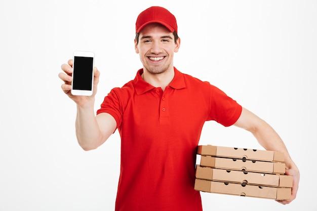 Foto de hombre feliz del servicio de entrega en camiseta roja y gorra con pila de cajas de pizza y mostrando teléfono inteligente, aislado sobre un espacio en blanco