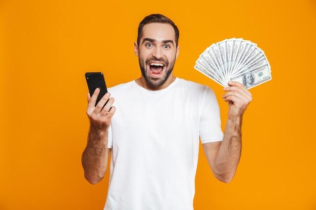 Foto de hombre guapo de 30 años en ropa casual con teléfono celular y ventilador de dinero, aislado