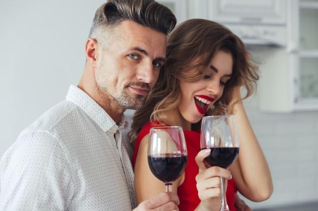 Foto de hombre guapo abrazo a su mujer mientras bebe vino