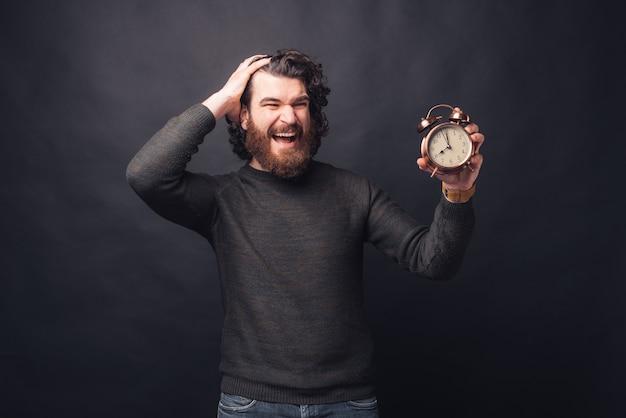 Foto de hombre guapo asustado mirando el despertador sobre fondo negro