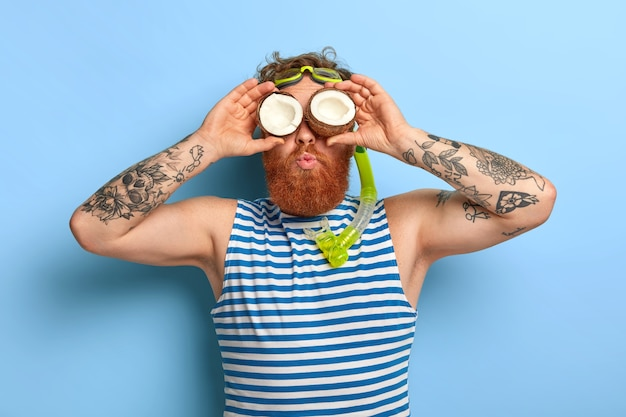 Foto de hombre guapo con barba que mantiene cocos en los ojos, mira con curiosidad a la distancia, quiere ver algo sobre el horizonte del mar, usa máscara de snorkel y chaleco a rayas, pasa las vacaciones de verano en el mar