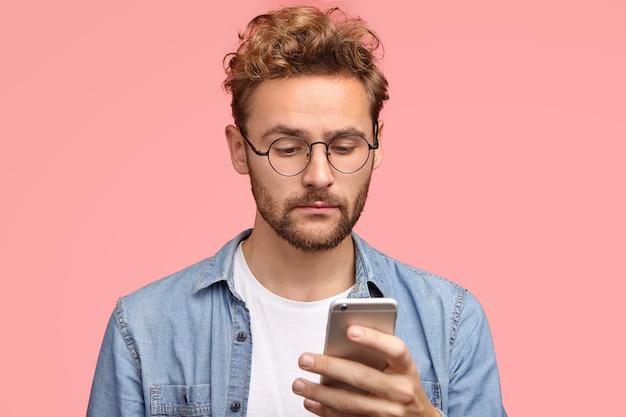 Foto de hombre guapo con cabello rizado, sostiene un teléfono celular moderno, escribe mensajes de texto, recibe notificación