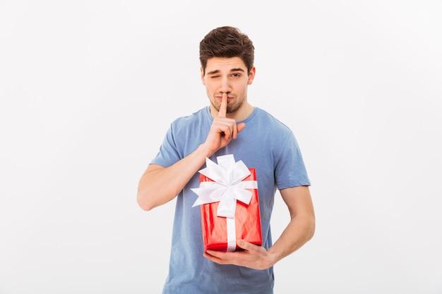 Foto de hombre guapo con regalo de cumpleaños y pidiendo mantener en secreto con el dedo en los labios, aislado sobre la pared blanca