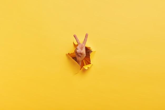 Foto de un hombre irreconocible que demuestra el signo de victroy a través del agujero rasgado en papel amarillo