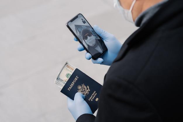 La foto del hombre irreconocible sigue las reglas de distanciamiento social, hace videollamadas, sostiene el teléfono móvil, el pasaporte con dinero usa guantes protectores y camina al aire libre en la calle. evitar el contacto con otras personas.