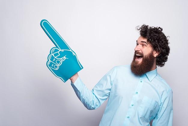 Foto de hombre joven emocionado con barba vistiendo camisa y apuntando hacia afuera con un guante de espuma de ventilador.