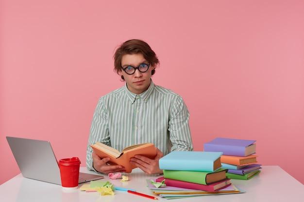 Foto de hombre joven con gafas viste camisa, el estudiante se sienta junto a la mesa y trabaja con el cuaderno, preparado para el examen, lee el libro, con mirada seria, aislado sobre fondo rosa.