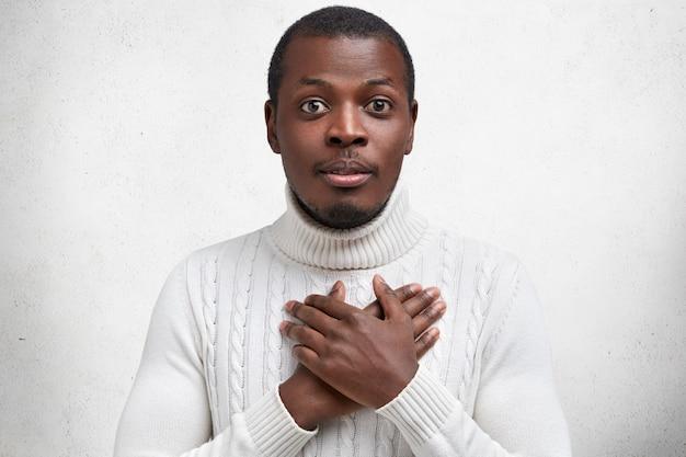 Foto de hombre joven y guapo de piel oscura tiene las manos en el pecho mientras expresa gratitud, estar satisfecho con la historia de la perforación del corazón