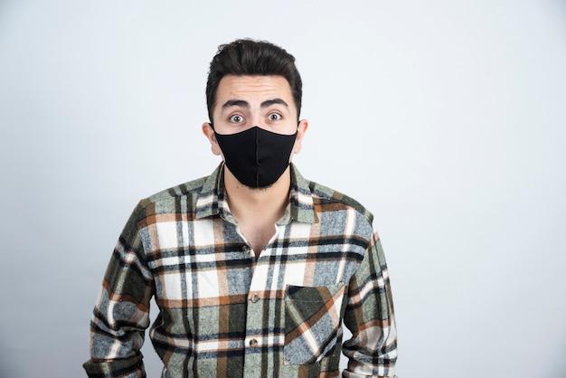 Foto de hombre joven con máscara negra para protección contra el coronavirus de pie sobre una pared blanca.