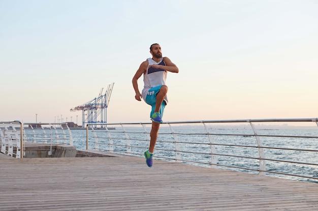 Foto de hombre joven saltando barbudo deportivo masculino haciendo estiramientos, ejercicios matutinos junto al mar, calentamiento después de correr.