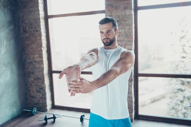 Foto de hombre macho preparándose para el entrenamiento matutino estirar los dedos de la mano músculos ropa deportiva pantalones cortos sin mangas zapatillas de deporte casa de entrenamiento grandes ventanas en el interior