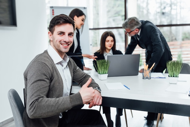 La foto en el hombre de negocios hermoso levanta su dedo en la oficina moderna.