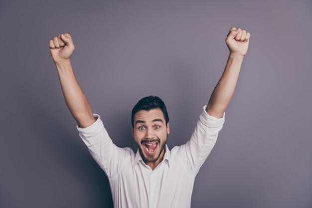 Foto de hombre de negocios macho joven manos levantadas celebrando el éxito