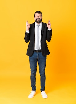 Foto de hombre de negocios sobre amarillo aislado con los dedos cruzados y deseando lo mejor