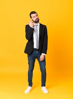 Foto de hombre de negocios sobre amarillo aislado con problemas para hacer el gesto de suicidio