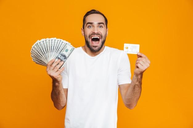 Foto de hombre optimista de 30 años en ropa casual con montón de dinero y tarjeta de crédito, aislado