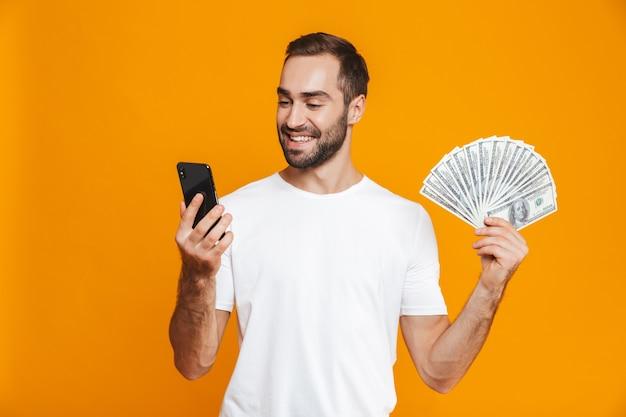 Foto de hombre optimista de 30 años en ropa casual con teléfono celular y ventilador de dinero, aislado