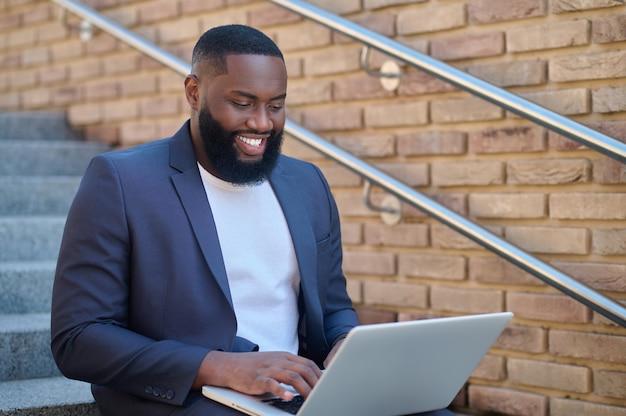 Una foto de un hombre de piel oscura con un traje y una computadora portátil.