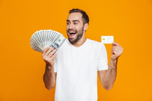 Foto de hombre positivo de 30 años en ropa casual con montón de dinero y tarjeta de crédito, aislado