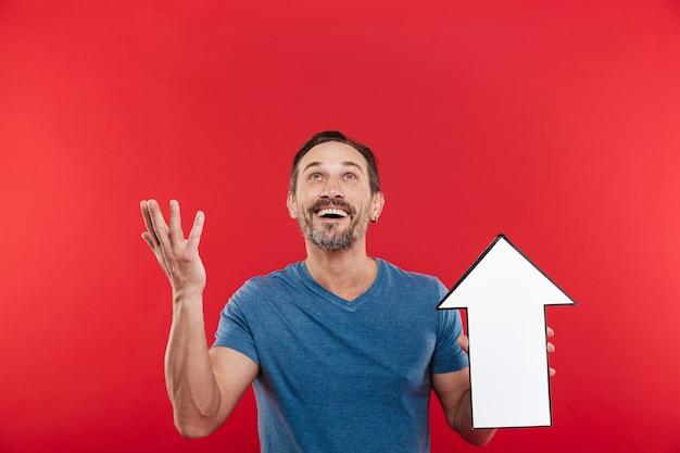 Foto de hombre satisfecho 30s con puntero de flecha de discurso en blanco que dirige hacia arriba en el espacio de la copia, aislado sobre fondo rojo.