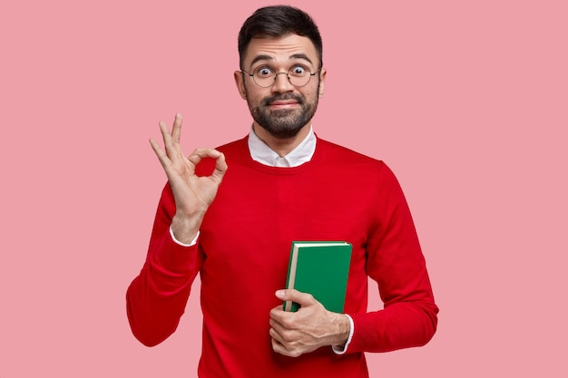 Foto de un hombre satisfecho sin afeitar que hace un buen gesto, se ve alegre, tiene una barba oscura, dice que todo está bien, sostiene un cuaderno