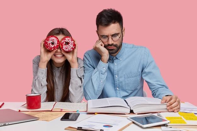 Foto de hombre serio sin afeitar usa anteojos para una buena visión, vestido con camisa formal, lee atentamente el libro, compañera de grupo femenina positiva se divierte
