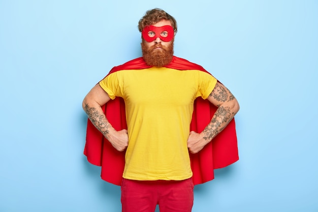Foto de hombre serio disfrazado de superhéroe, mantiene las manos en la cintura, posee talentos extraordinarios