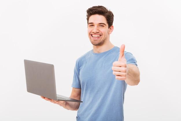 Foto de hombre sonriente en camiseta casual sosteniendo portátil plateado y gesticulando pulgar hacia arriba, aislado sobre la pared blanca