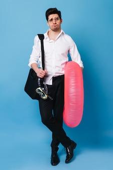 Foto de hombre en traje de negocios, reunido en viaje al mar. chico con gafas posa con máscara de buceo, colchón inflable y bolsa con documentos.