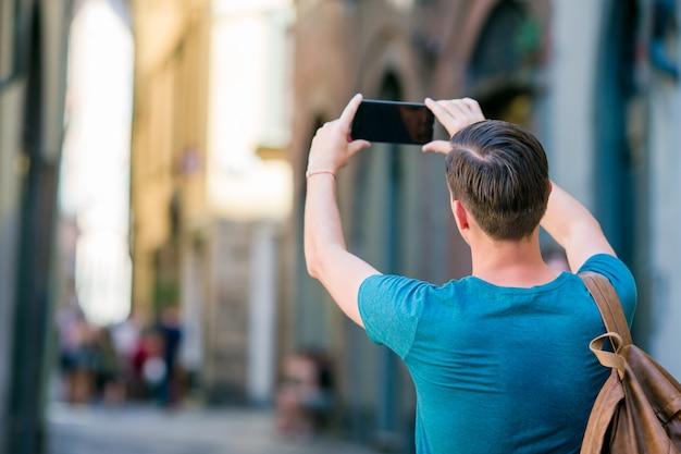 Foto de hombre turista tomando por teléfono inteligente en manos caminando por las estrechas calles italianas en europa. joven urbano de vacaciones explorando ciudad europea