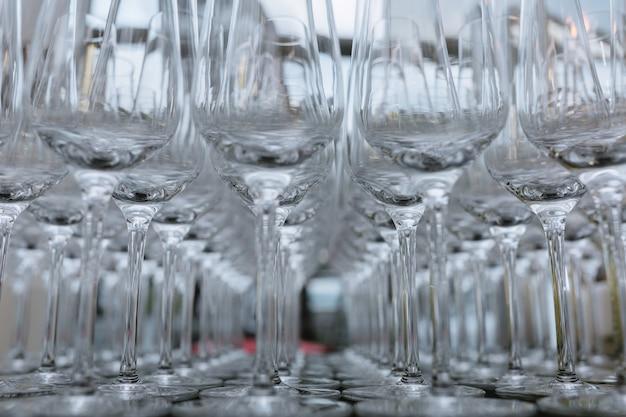 Foto horizontal de copas de vino vacías alineadas, primer plano, negro