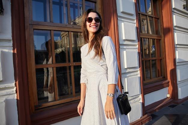 Foto horizontal de encantadora joven mujer morena con peinado casual en gafas de sol mirando a un lado y sonriendo positivamente mientras camina por la ciudad en un cálido día de primavera