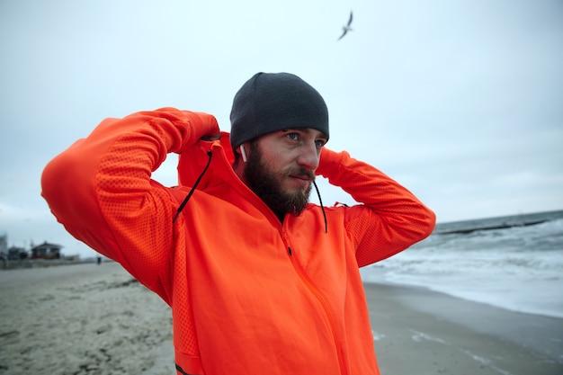 Foto horizontal de hombre barbudo joven guapo vestido con ropa deportiva sosteniendo capucha con las manos levantadas y mirando al mar con rostro tranquilo, caminando junto al mar antes de la jornada laboral