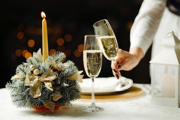 Foto horizontal de la mano de la mujer sosteniendo copas de champán, luces de velas el concepto de cena romántica.