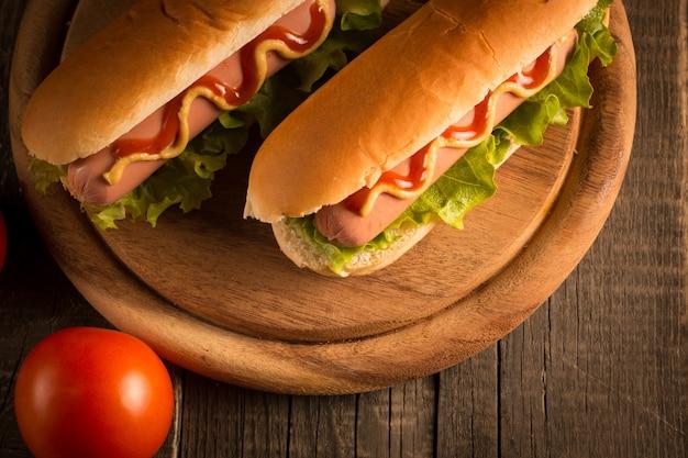 Foto de hot dog con mostaza amarilla y salsa de tomate.