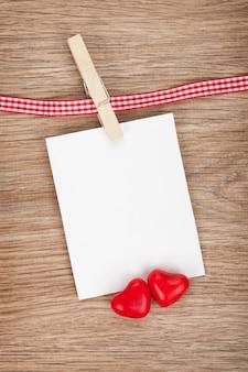 Foto instantánea en blanco con corazones de caramelo. sobre fondo de madera