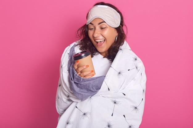 Foto interior de una adorable mujer sosteniendo una taza de café responsable, la niña encantadora se despierta por la mañana, mirando emocionada su taza de papel