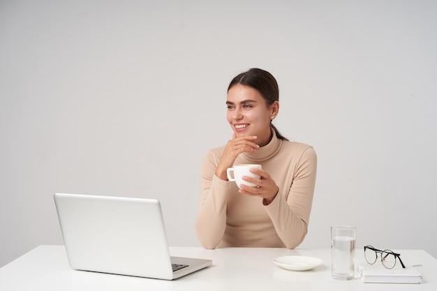Foto interior de una encantadora joven mujer de cabello oscuro mirando soñadoramente a un lado y sonriendo ampliamente, bebiendo una taza de café mientras trabaja en la oficina con un portátil moderno