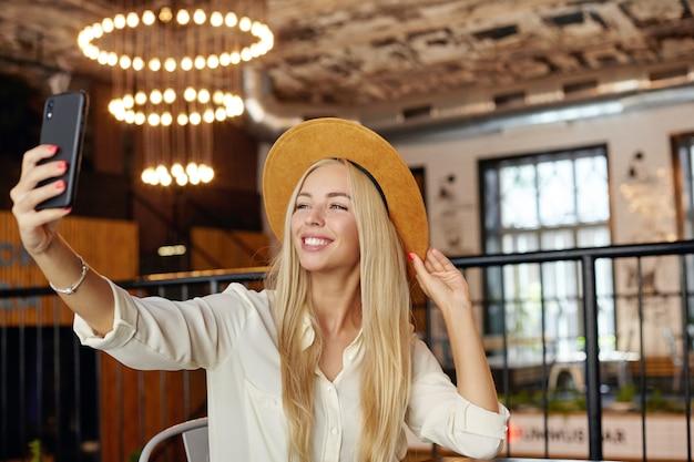 Foto interior de la encantadora joven rubia de pelo largo con sombrero marrón posando en la mesa de la cafetería, manteniendo el teléfono móvil en la mano y mirando con alegría
