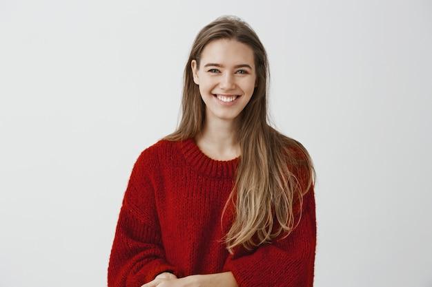 Foto interior de una encantadora mujer europea de aspecto amable con elegante suéter holgado, hablando casualmente con un compañero de trabajo durante el descanso en el trabajo, sonriendo ampliamente, encantada y entusiasmada con la conversación
