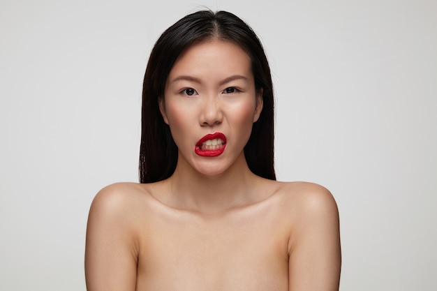 Foto interior de una hermosa joven de pelo oscuro con peinado casual torciendo la boca mientras, posando sobre una pared blanca con los hombros desnudos