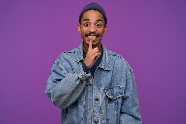Foto interior de un joven moreno con barba bonita sosteniendo el dedo índice en sus labios mientras mira, llamando a mantener el secreto, de pie sobre la pared púrpura
