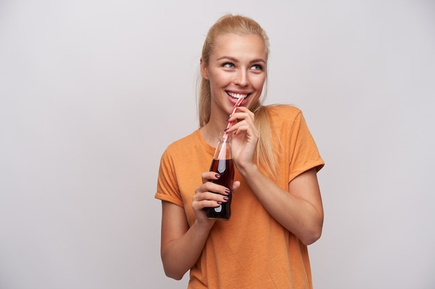 Foto interior de joven mujer rubia alegre con peinado de cola de caballo sosteniendo una botella de vidrio de soda en manos levantadas y mirando alegremente a un lado, aislado sobre fondo blanco.