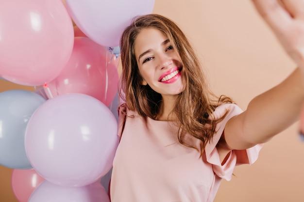 Foto interior de linda mujer con peinado largo haciendo selfie después de la fiesta de cumpleaños