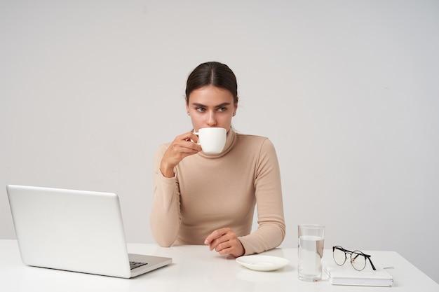 Foto interior de una mujer bastante joven de pelo oscuro en ropa formal bebiendo una taza de té y mirando pensativamente frente a sí misma, sentada en la mesa sobre una pared blanca
